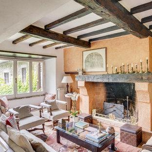Ispirazione per un soggiorno mediterraneo con sala formale, pareti arancioni, camino classico, nessuna TV e travi a vista