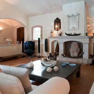 Ispirazione per un grande soggiorno mediterraneo aperto con pareti bianche, pavimento in terracotta, camino classico, cornice del camino in pietra, porta TV ad angolo e pavimento rosa