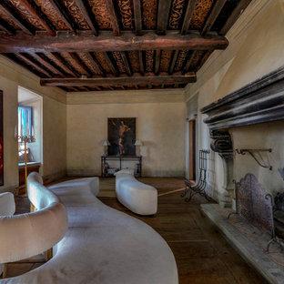 Ispirazione per un soggiorno mediterraneo chiuso con pareti beige, parquet scuro, camino classico, pavimento marrone e travi a vista