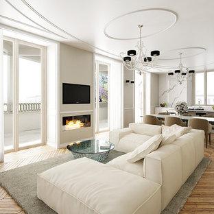 Offenes Modernes Wohnzimmer mit braunem Holzboden, Gaskamin, Kaminumrandung aus Stein und verstecktem TV in Mailand