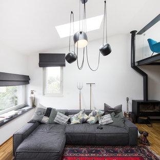 Immagine di un soggiorno design con pareti bianche, pavimento in legno massello medio, stufa a legna e pavimento marrone