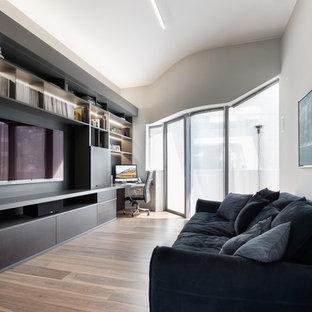 Immagine di un soggiorno design chiuso con pareti grigie, pavimento in legno massello medio, parete attrezzata e pavimento marrone