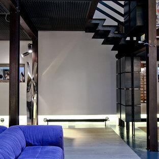 Inredning av ett industriellt stort allrum på loftet, med ett musikrum, vita väggar, ljust trägolv och en dold TV