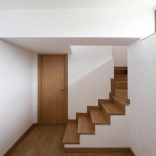 Aménagement d'un petit sous-sol scandinave semi-enterré avec un mur blanc, un sol en bois brun et aucune cheminée.