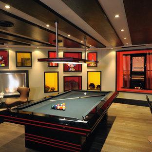 Cette image montre un sous-sol design avec un mur beige, un sol en bois clair, une cheminée ribbon et un manteau de cheminée en métal.