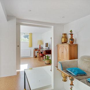 Réalisation d'un sous-sol design avec un mur blanc, un sol en liège et un sol beige.