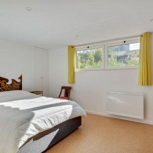 Idée de décoration pour un sous-sol design avec un mur blanc, un sol en liège et un sol beige.