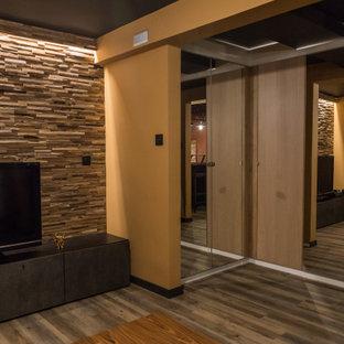 Aménagement d'un sous-sol craftsman en bois avec salle de jeu, un mur jaune et un sol en bois brun.