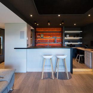 Cette image montre un sous-sol design de taille moyenne et enterré avec un mur noir, un sol en bois brun et aucune cheminée.