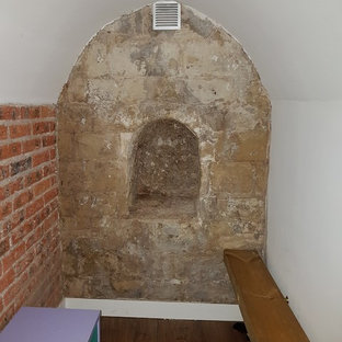 Cette image montre un petit sous-sol design enterré avec un mur blanc, un sol en linoléum et un sol marron.