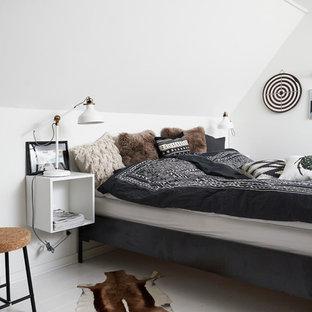 Immagine di una camera da letto scandinava con pareti bianche e pavimento in legno verniciato