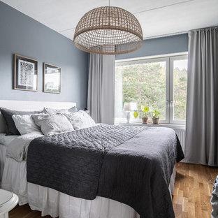 Bild på ett skandinaviskt sovrum, med blå väggar, mellanmörkt trägolv och brunt golv
