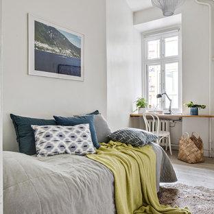 Nordisk inredning av ett gästrum, med vita väggar, målat trägolv och vitt golv