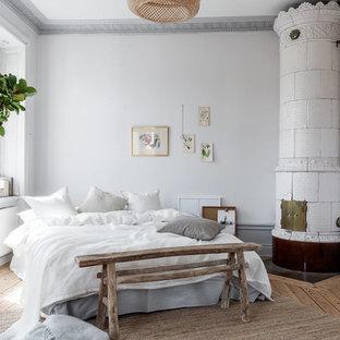 Inredning av ett minimalistiskt mellanstort huvudsovrum, med grå väggar, ljust trägolv, en öppen hörnspis och beiget golv