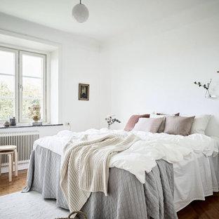 Inspiration för mellanstora skandinaviska huvudsovrum, med vita väggar, mellanmörkt trägolv och brunt golv