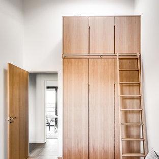 Inredning av ett modernt sovrum, med vita väggar, ljust trägolv och beiget golv