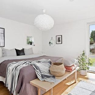 Foto på ett skandinaviskt sovrum, med vita väggar och ljust trägolv