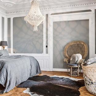 Idéer för att renovera ett skandinaviskt huvudsovrum, med grå väggar, mellanmörkt trägolv och brunt golv