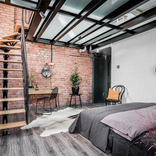 Idées déco pour une chambre parentale industrielle de taille moyenne avec un mur orange, un sol en bois brun et un sol gris.