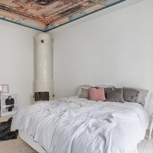 Inredning av ett shabby chic-inspirerat sovrum, med en öppen vedspis, vita väggar, ljust trägolv, en spiselkrans i metall och beiget golv