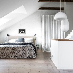 Foto på ett mellanstort skandinaviskt huvudsovrum, med vita väggar och ljust trägolv