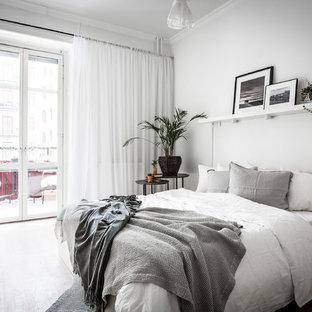 Inspiration för mellanstora skandinaviska huvudsovrum, med vita väggar och ljust trägolv