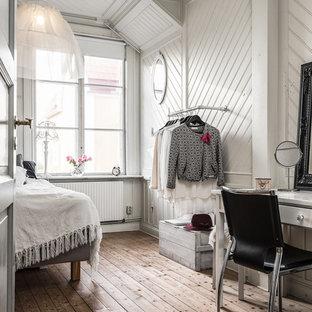 Foto på ett shabby chic-inspirerat sovrum, med vita väggar och brunt golv
