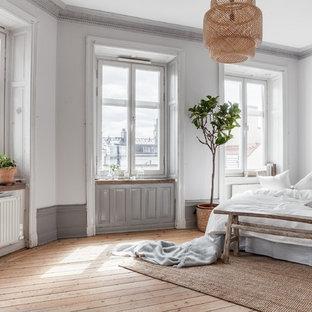 ストックホルムの広い北欧スタイルのおしゃれな主寝室 (白い壁、淡色無垢フローリング)