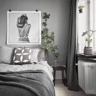 Immagine di una camera degli ospiti nordica di medie dimensioni con pareti grigie e parquet chiaro