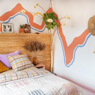 Imagen de dormitorio ecléctico con paredes multicolor y suelo rosa