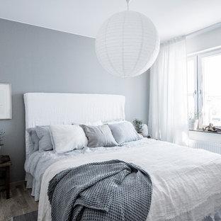 Foto på ett mellanstort skandinaviskt sovrum, med grå väggar, mellanmörkt trägolv och grått golv