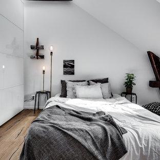 Idéer för ett mellanstort skandinaviskt sovrum, med vita väggar och mellanmörkt trägolv