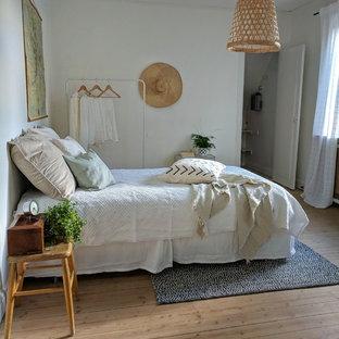 Idéer för nordiska sovrum, med vita väggar, mellanmörkt trägolv och brunt golv