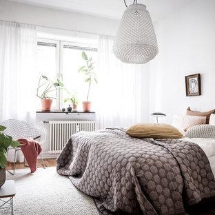 Idéer för ett nordiskt gästrum, med vita väggar, mellanmörkt trägolv och brunt golv
