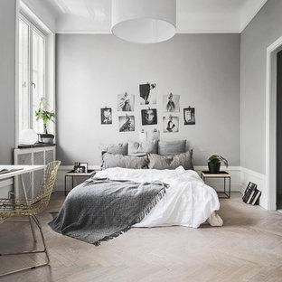 Ejemplo de dormitorio principal, escandinavo, de tamaño medio, con paredes grises y suelo de madera clara
