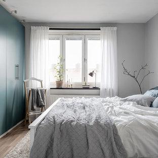 Exempel på ett skandinaviskt huvudsovrum, med grå väggar och ljust trägolv