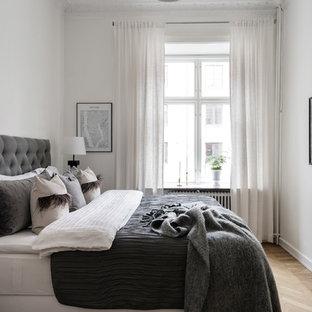 Exempel på ett klassiskt sovrum, med vita väggar, ljust trägolv och beiget golv