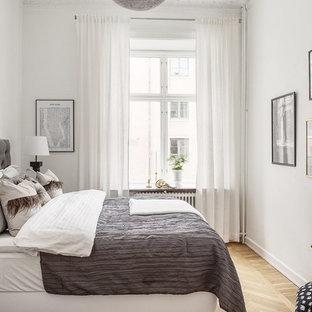 Nordisk inredning av ett gästrum, med vita väggar, ljust trägolv och beiget golv