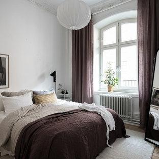 Bild på ett minimalistiskt sovrum, med vita väggar, ljust trägolv och beiget golv