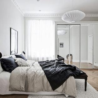 Foto på ett nordiskt huvudsovrum, med grå väggar, ljust trägolv och beiget golv