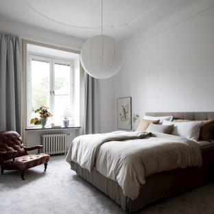 Foto på ett minimalistiskt sovrum, med vita väggar, heltäckningsmatta och grått golv