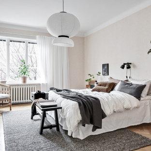 Foto på ett stort skandinaviskt huvudsovrum, med beige väggar, mellanmörkt trägolv och beiget golv