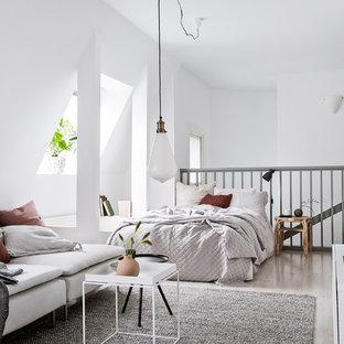 Idéer för ett litet minimalistiskt sovrum, med vita väggar, ljust trägolv och beiget golv