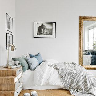 Skandinavisk inredning av ett sovrum, med vita väggar och mellanmörkt trägolv