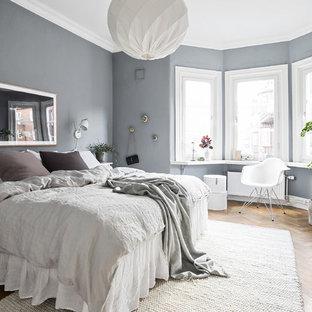 Idéer för ett nordiskt huvudsovrum, med grå väggar, mellanmörkt trägolv och brunt golv