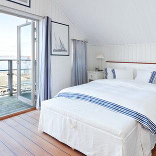 Idéer för mellanstora maritima sovrum, med vita väggar och mellanmörkt trägolv