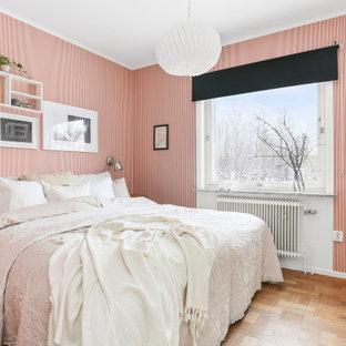 Réalisation d'une chambre nordique de taille moyenne avec un mur rouge, un sol en bois brun, aucune cheminée et un sol marron.