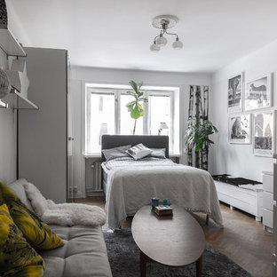 Minimalistisk inredning av ett mellanstort huvudsovrum, med vita väggar, ljust trägolv och beiget golv