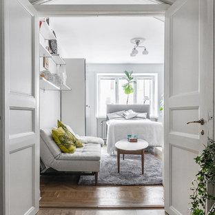 Bild på ett mellanstort minimalistiskt sovrum, med vita väggar, mellanmörkt trägolv och brunt golv
