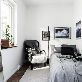 Diseño de habitación de invitados nórdica con paredes blancas y suelo de madera oscura